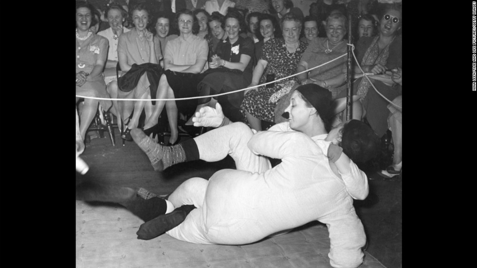 "The entertainment included a mock wrestling match. Joan Thornwaite (back to camera) ""won by tickling in five minutes."" Her opponent wears a fake mustache held on with chewing gum."