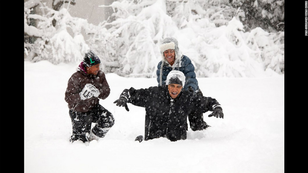 Obama and his daughters, Sasha and Malia, play in a snowstorm at the White House on February 6, 2010.