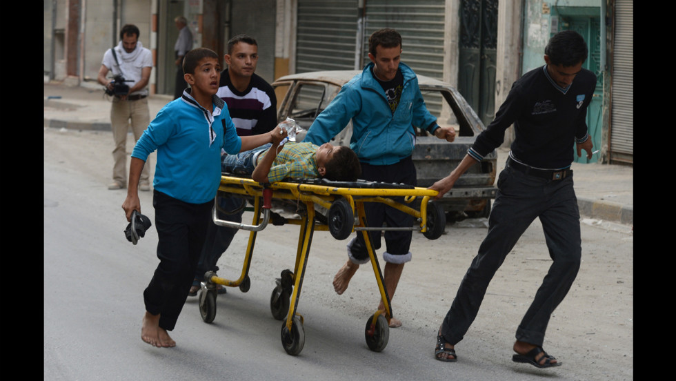 Relatives wheel a injured boy outside a hospital on Tuesday in Aleppo.