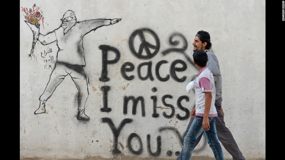 Syrian youths walk past graffiti in the rebel-held city of Minbej on Wednesday.