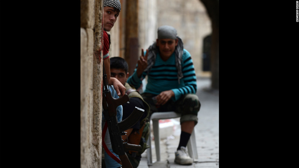 A Syrian opposition fighter flashes the sign for victory as he guards a post with his comrades in Aleppo on Thursday.