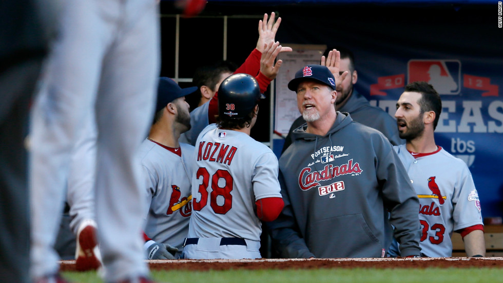 Pete Kozma of the St. Louis Cardinals is congratulated by hitting coach Mark McGwire in the dugout after Kozma scored on a sacrifice fly in the top of the third inning against the Washington Nationals.