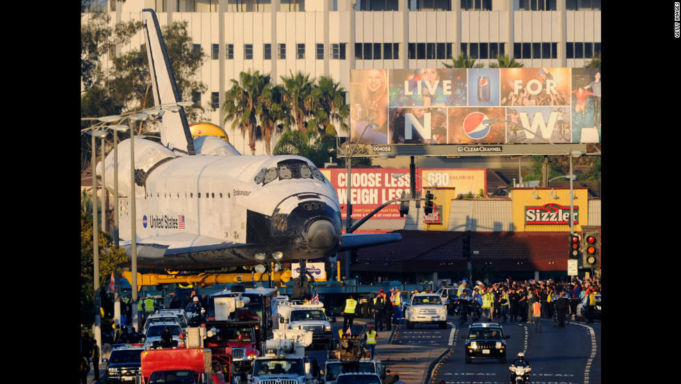 The space shuttle Endeavour is transported to The Forum arena for a stopover and celebration on Saturday.