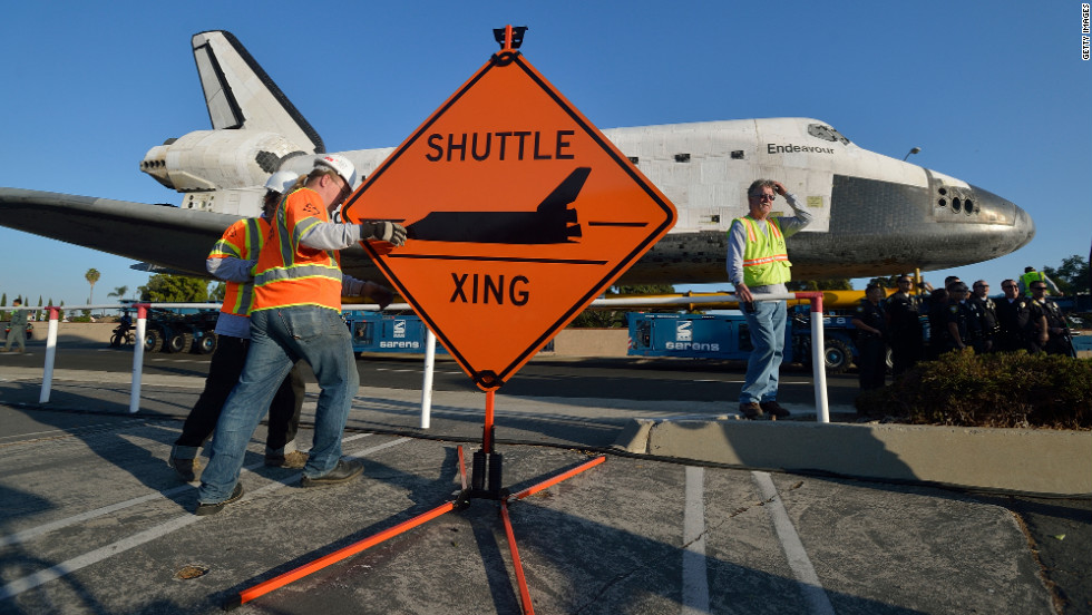 "Work crews set up a ""Shuttle Xing"" sign on Saturday."