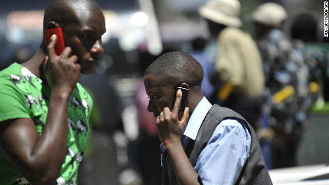 People walk while speaking on the phone on October 1,2012 in Nairobi.