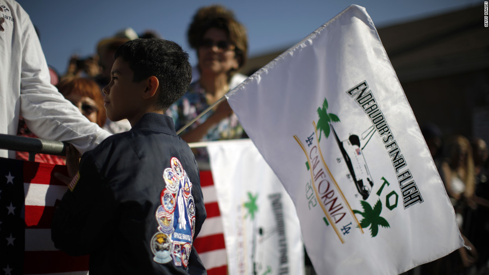 Kevin Alcaraz, 8, waves a flag from the crowd gathered along the shuttle's route.
