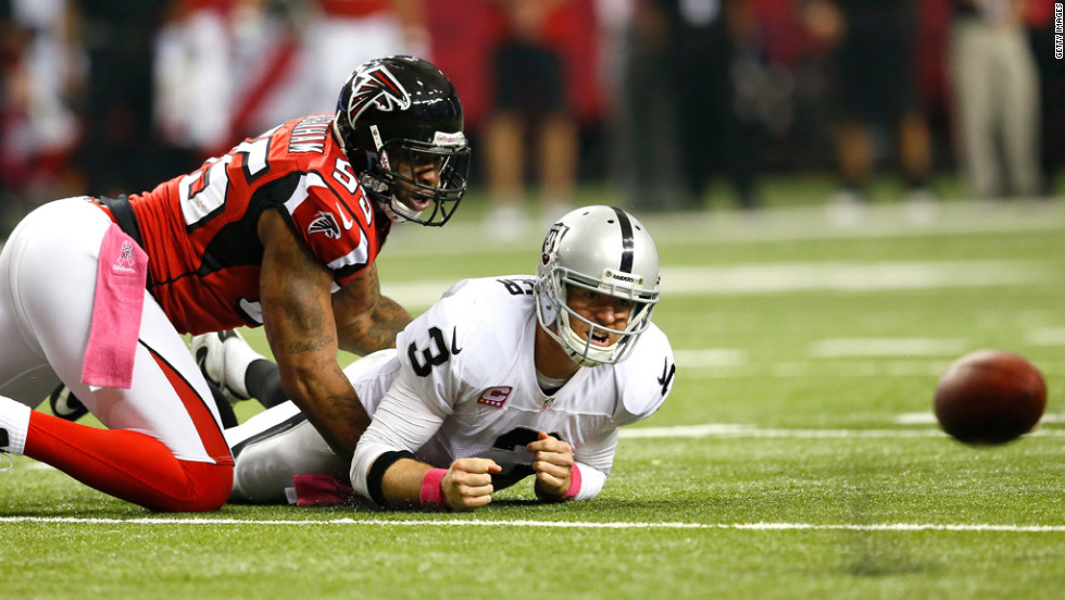 John Abraham of the Atlanta Falcons forces a fumble and turnover by Carson Palmer of the Oakland Raiders on Sunday at the Georgia Dome in Atlanta.