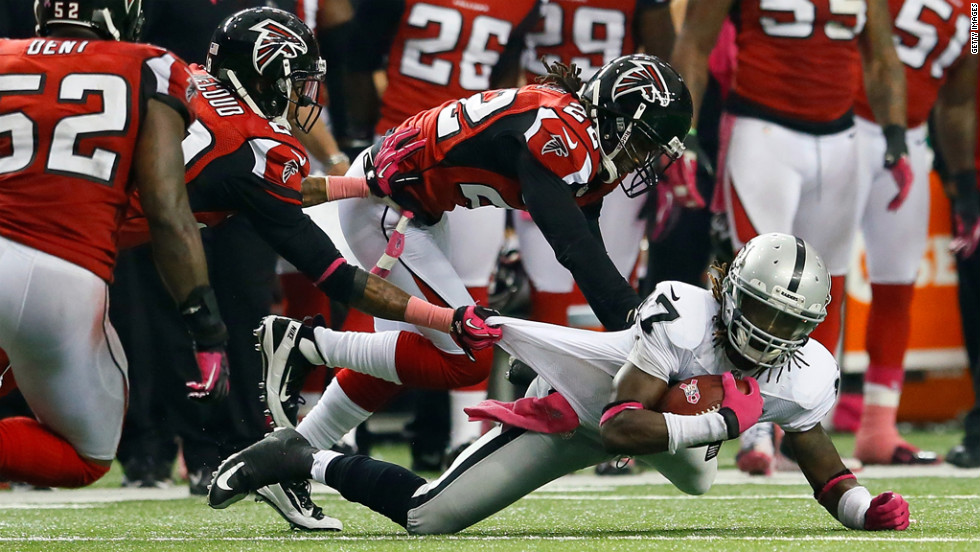 Denarius Moore of the Raiders is tackled by Falcons defenders on Sunday.,