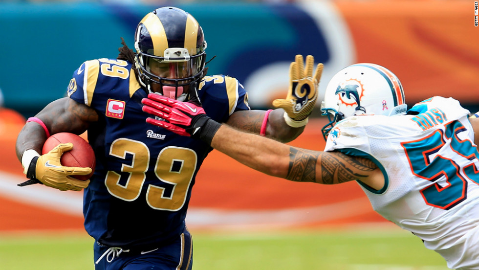 Steven Jackson of the St. Louis Rams tries to break a tackle by Koa Misi of the Miami Dolphins.