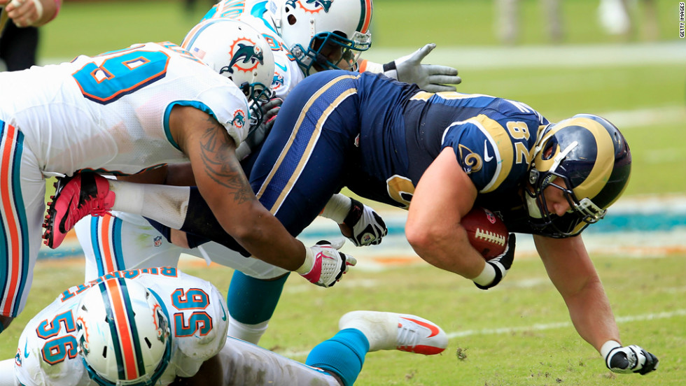 Dolphins defenders tackle Matthew Mulligan of the Rams.