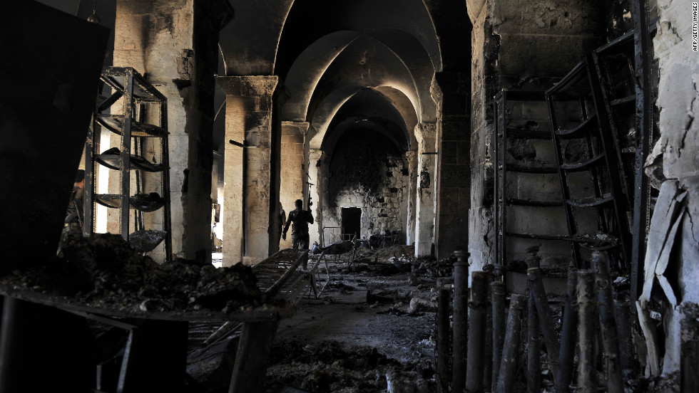 A Syrian rebel walks inside a burnt section of the Umayyad Mosque. Opposition activists reported that the 12th-century mosque was set afire during heavy fighting on Saturday, October 13.