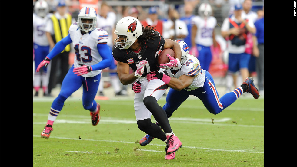 Larry Fitzgerald of the Cardinals breaks a tackle by George Wilson of the Bills.