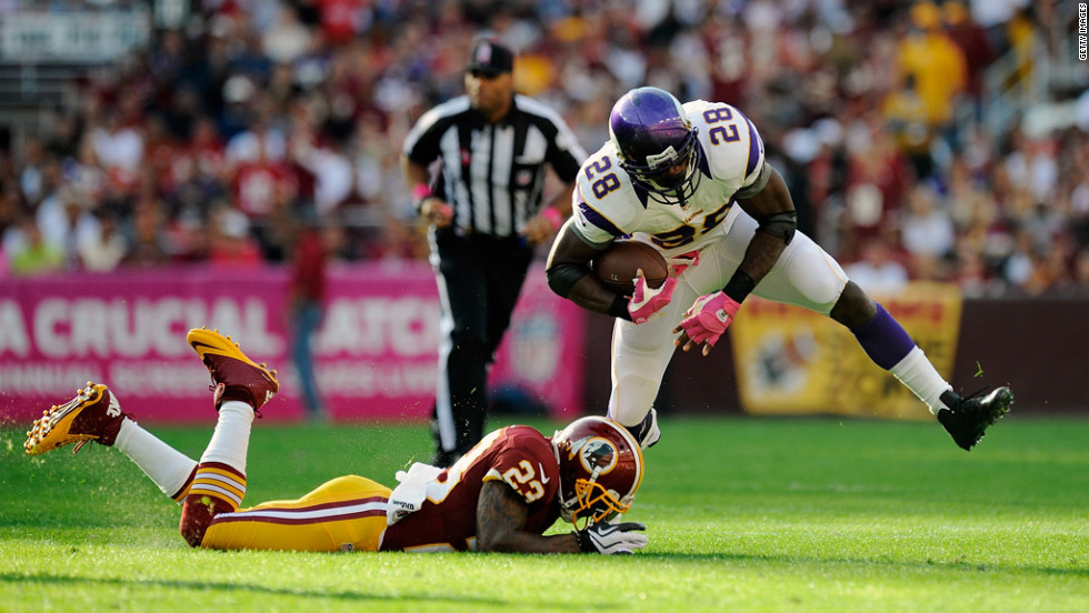 Adrian Peterson of the Vikings avoids a tackle by DeAngelo Hall of the Redskins in the first half.