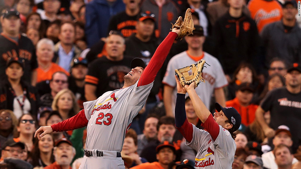 David Freese of the Cardinals catches a fly ball over teammate Pete Kozma to end the third inning of Game One.