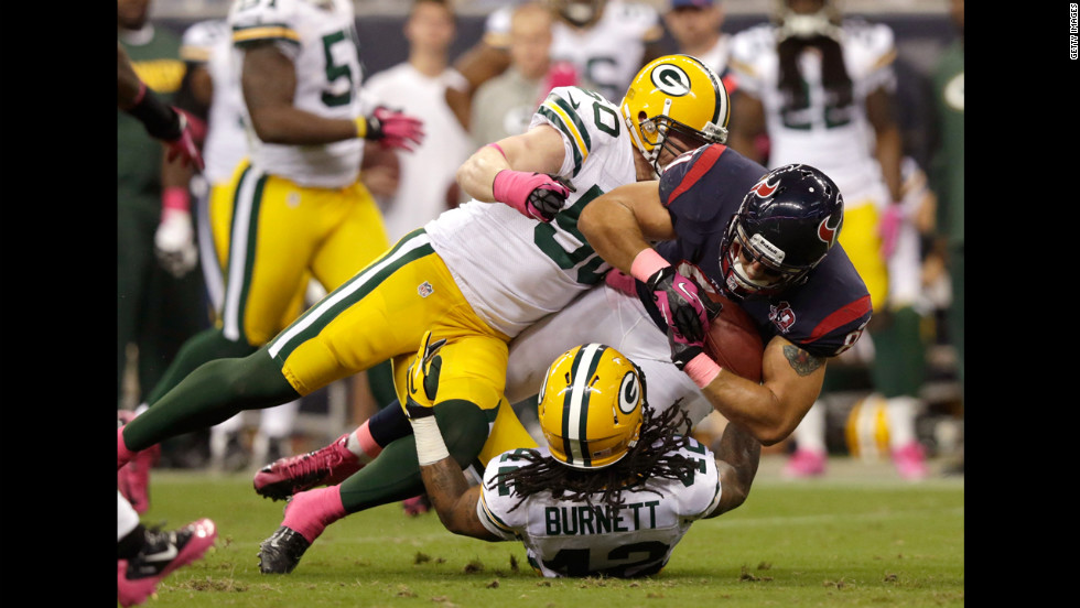 Owen Daniels of the Texans is tackled by A.J. Hawk, left, and Morgan Burnett of the Packers.