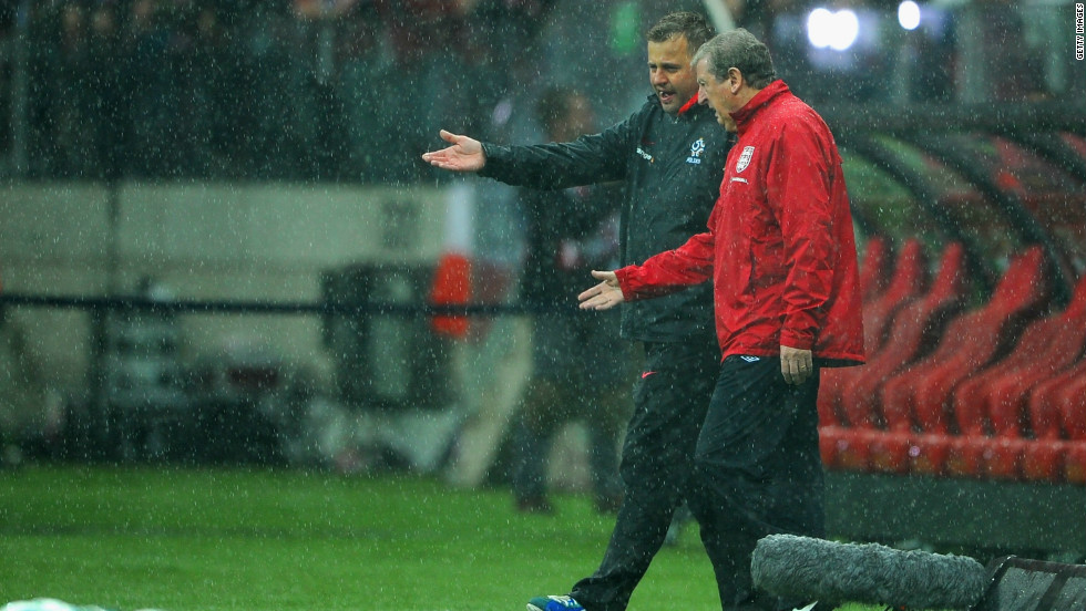 England manager Roy Hodgson speaks to a member of the Polish coaching staff as the rain continues to fall in Warsaw with the surface deemed to be unplayable.