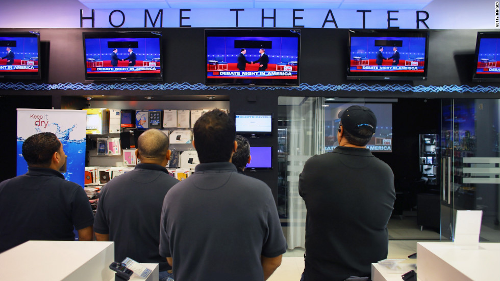 A group of men watch the presidential debate on television screens at an electronics store in Miami on Tuesday, October 16.