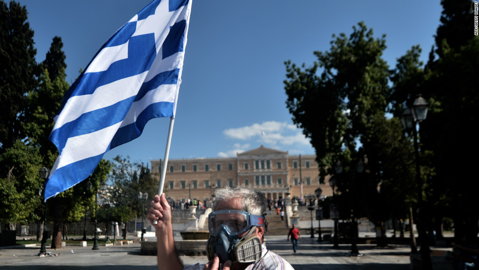A demonstrator wearing a gas mask waves a Greek flag during clashes between police and anti-austerity protestors in Athens. Police fired tear gas to disperse demonstrators after they broke through a police line outside luxury hotels on central Syntagma Square.