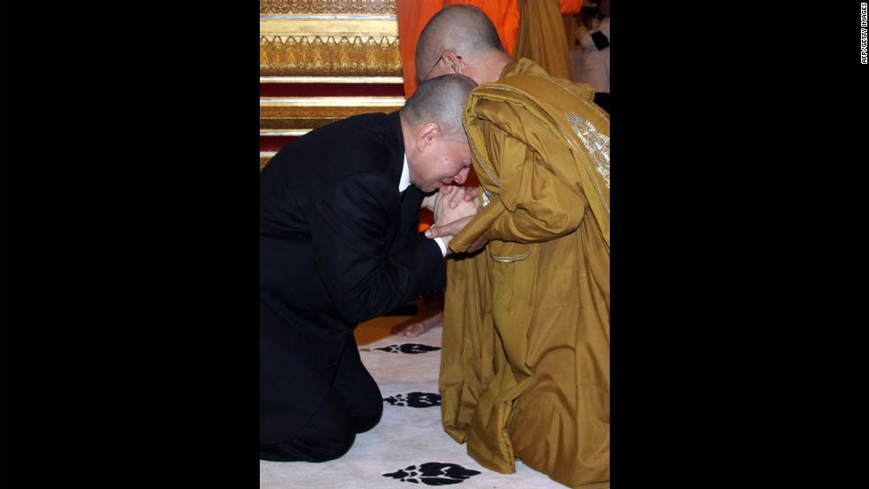 Cambodian King Sihamoni cries as he shakes hands with a Buddhist monk at the royal palace in Phnom Penh.