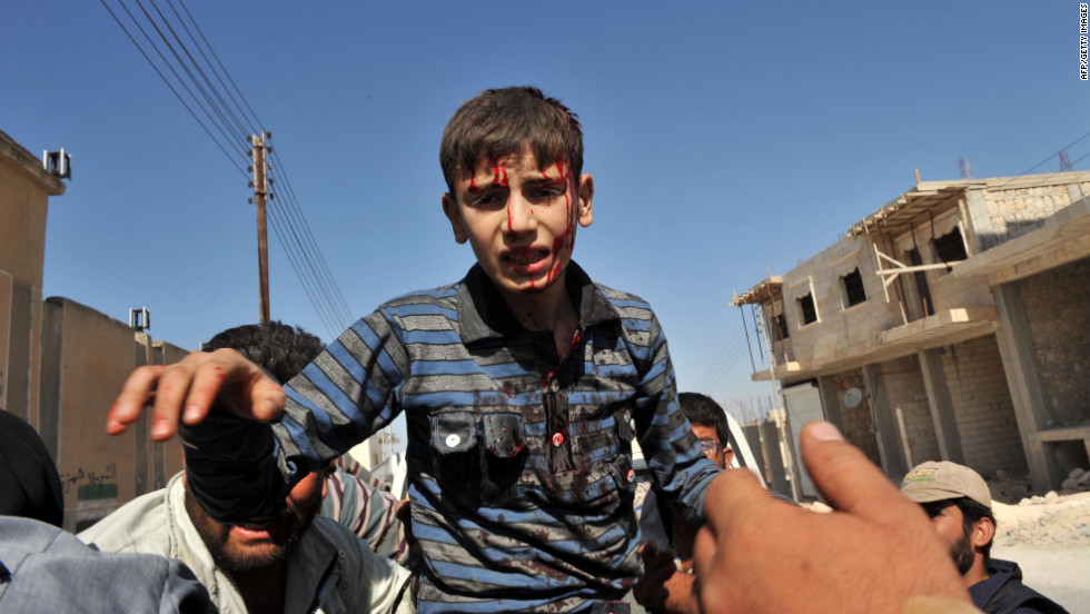 A wounded Syrian boy is carried to the hospital following Thursday's airstrike in Maaret al-Numaan.