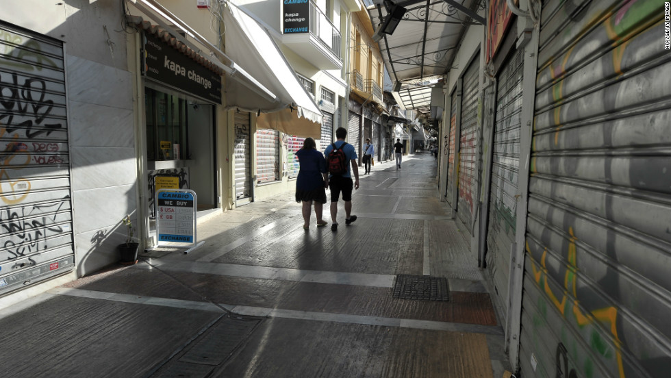 People walk by closed shops in Athens during the 24-hour strike. Greece's fourth national strike this year brought the country to a virtual standstill and shut down most of the transport system.