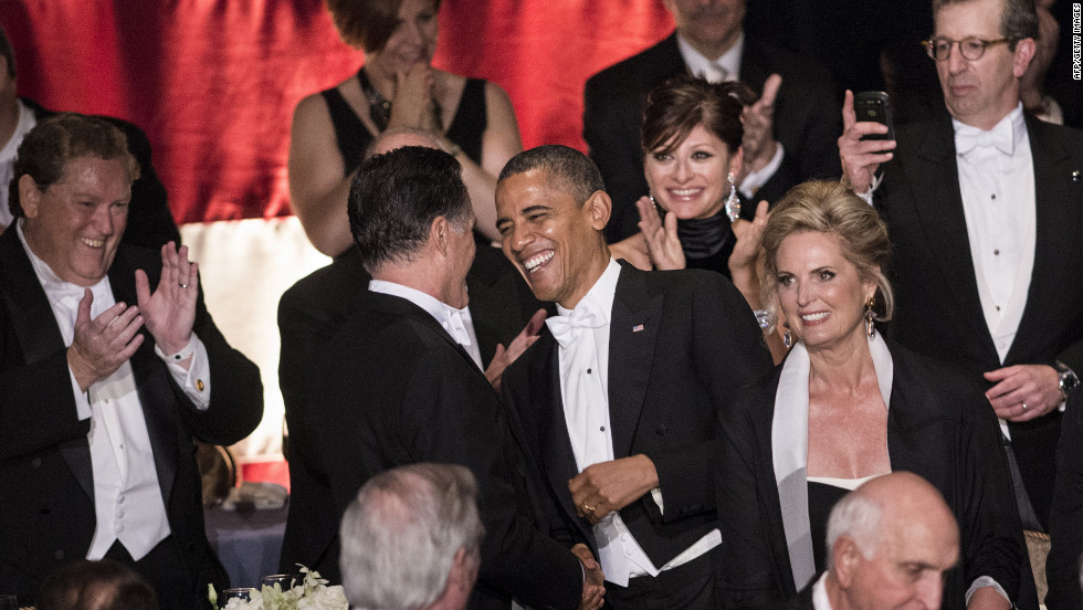 President Barack Obama and Mitt Romney greet one another as Ann Romney, right, stands nearby.