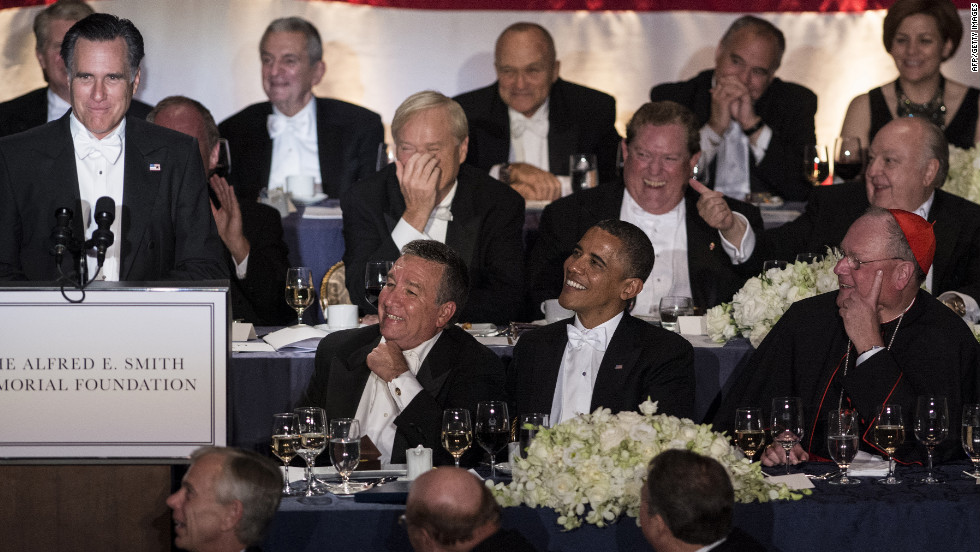 President Barack Obama and others listen as Republican presidential candidate Mitt Romney speaks.