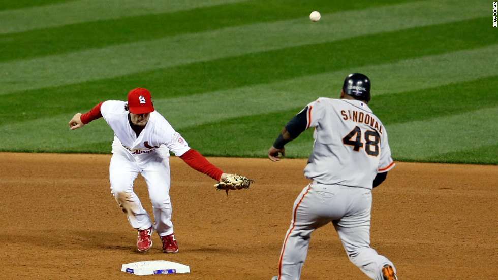 No. 38 Pete Kozma of the Cardinals is unable to field a throw by No. 31 pitcher Lance Lynn as No. 48 Pablo Sandoval of the Giants rounds second base in the fourth inning.