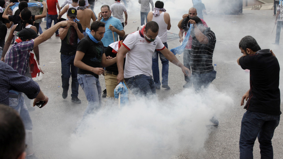 Protesters react to tear gas being fired at them by Lebanese police officers on Sunday.