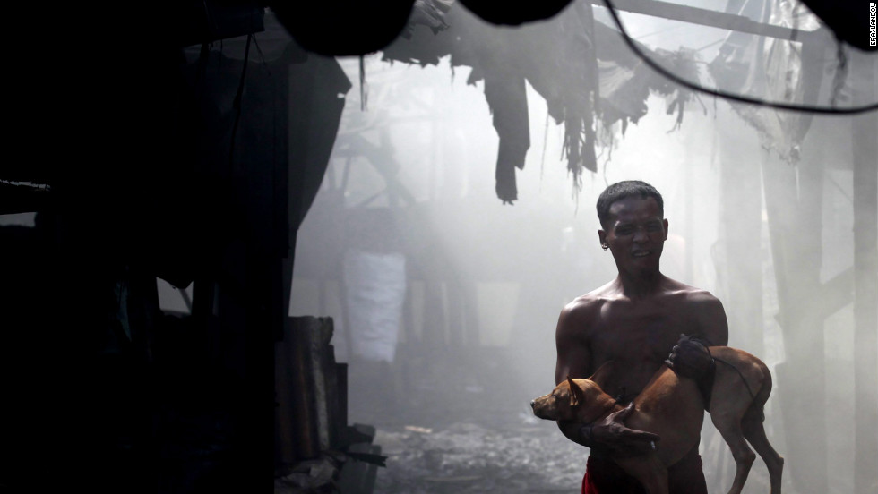 A man carries his dog amid thick ash and smoke. Many residents of the slum admit that they often get sick from burning wood to make charcoal.