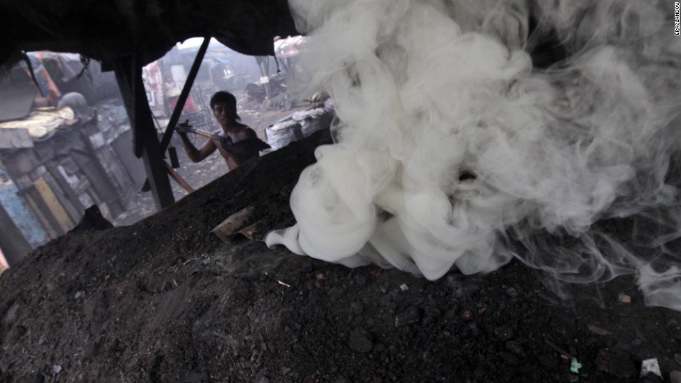 A worker prepares materials to burn to produce charcoal at the makeshift factory. The 15-year-old industry produces 6,000 sacks of charcoal monthly.