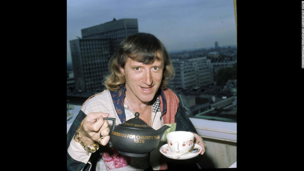 Savile pours a cup of tea.