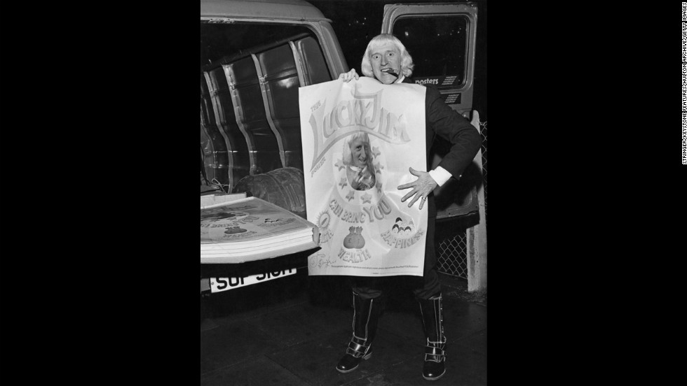 "Savile holds a newly-printed ""Lucky Jim"" poster. The posters feature a portrait of the DJ, along with a text reading: ""The Lucky Jim poster can bring you health, wealth, happiness. This is a genuine duplicate signature and what's more Jimmy has actually touched YOUR poster!"""