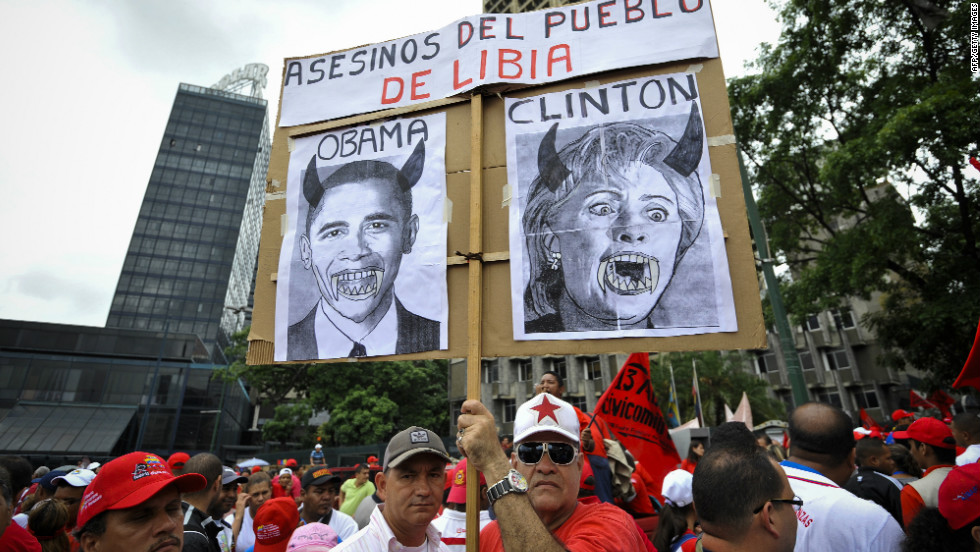"Despite Chavez's recent endorsement of Obama, not everyone approves of the job Washington is doing. Here, protesters hold a poster reading ""killers of Libyan people"" with portraits of Barack Obama and Hillary Clinton in Caracas, Venezuela, on April 13, 2011."