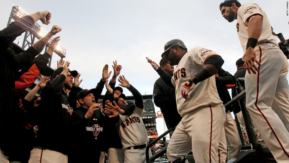 Sandoval celebrates with teammates in the dugout after scoring on a solo home run to center field.