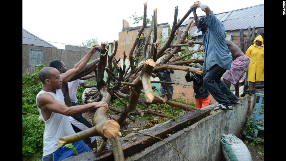Men deal with downed tree branches after heavy rain caused by Hurricane Sandy in Kingston, Jamaica, on Wednesday, October 24.