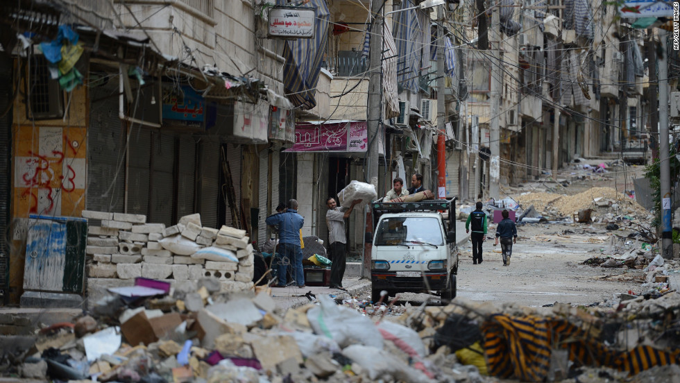 Civilians carry their belongings along a street strewn with garbage and debris following fighting between Syrian government troops and rebel fighters in the Salaheddin district  of Aleppo, Syria, on October 25.