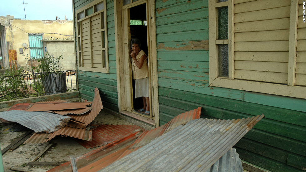 A woman peers out the door of her house Thursday after it was damaged by Hurricane Sandy in Bayamo, Cuba.