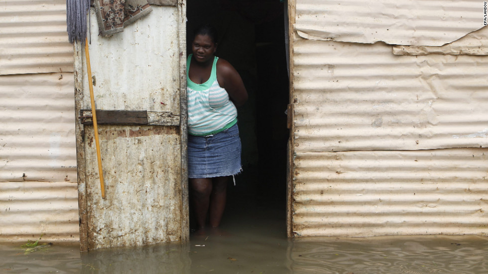 A woman stands at the entrance of her house surrounded by flood water after heavy rain in Santo Domingo on Thursday.