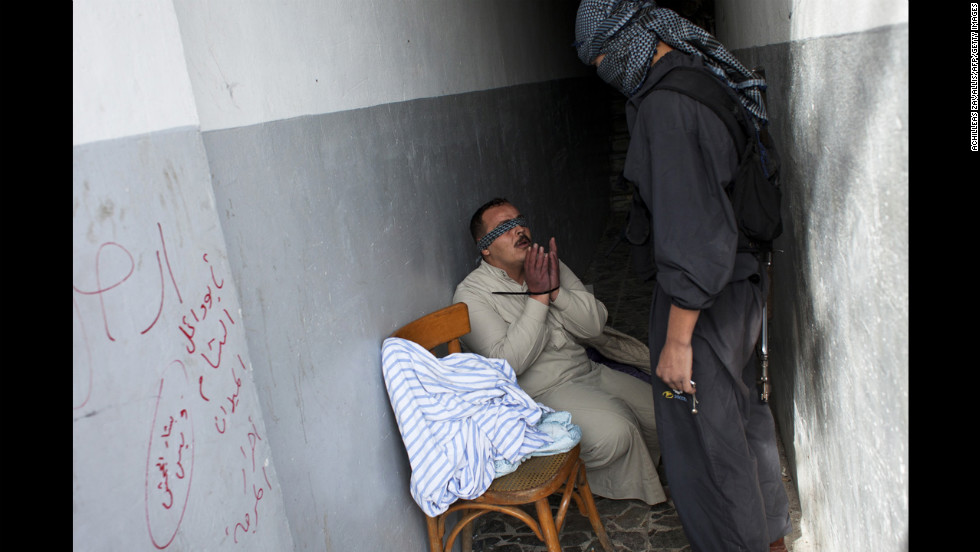 A Syrian rebel interrogates a handcuffed and blindfolded man suspected of being a pro-regime militiaman after he was detained by the Free Syria Army in Aleppo on Friday, October 26.