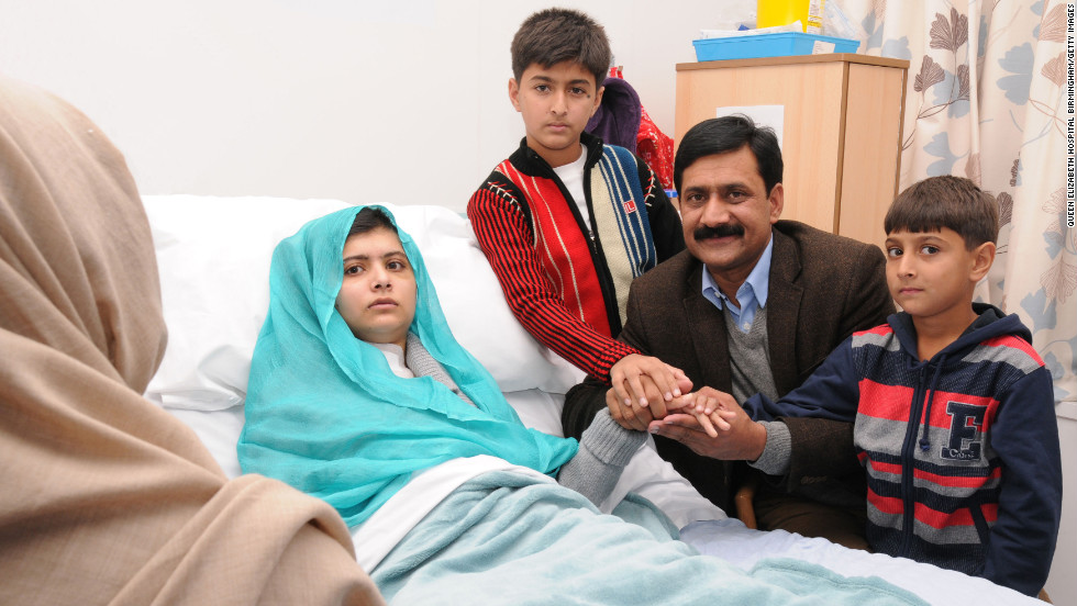 Malala sits up in her hospital bed with her father, Ziauddin, and her two younger brothers, Atal Khan, right, and Khushal Khan on Friday, October 26, 2012, at the Queen Elizabeth Hospital Birmingham in Birmingham, England.