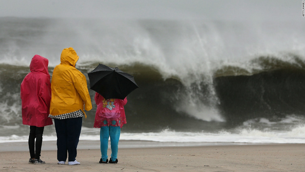 People stand on the beach watching the heavy surf caused by the approaching hurricane on Sunday in Cape May.