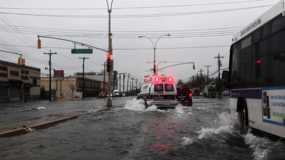 An ambulance maneuvers through water on Rockaway Beach Boulevard in Queens as the weather sours Monday in New York City.