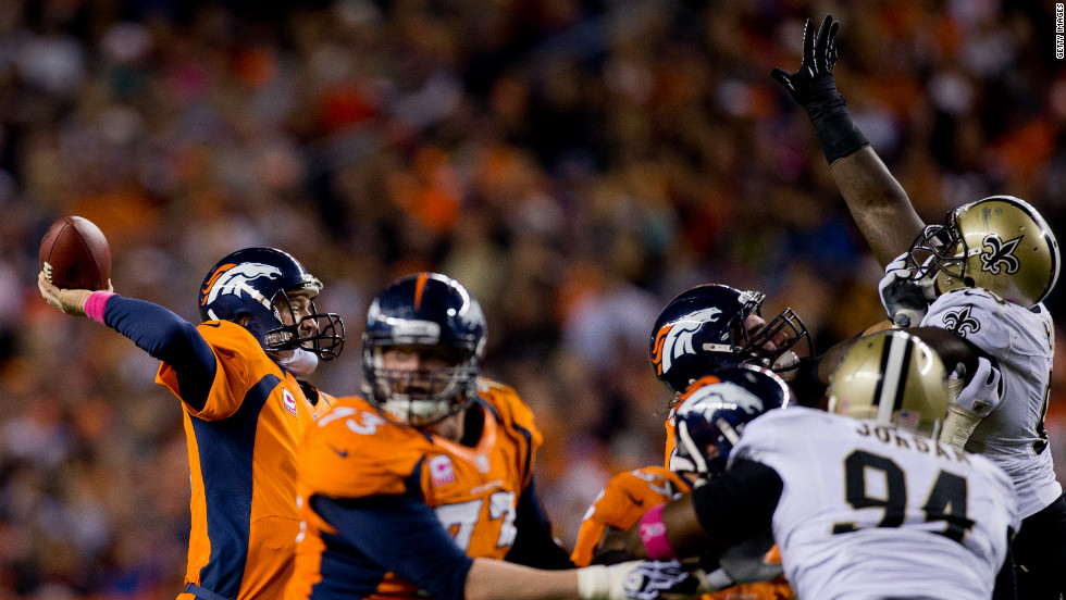 Quarterback Peyton Manning of the Broncos throws a pass over the outstretched arms of the Saints defense during the second quarter on Sunday.