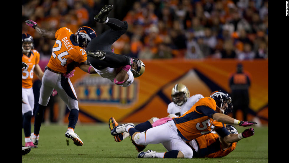 Running back Pierre Thomas of the Saints is upended by cornerback Champ Bailey of the Broncos during the second quarter.
