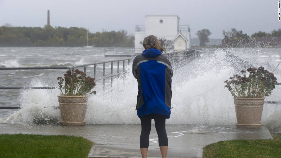 A woman watches waves crash onto a pier on New York's City Island on Monday. Residents were ordered to evacute the island.