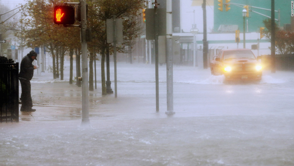 A man stands on the sidewalk Monday as a vehicle drives up a flooded street in Atlantic City.