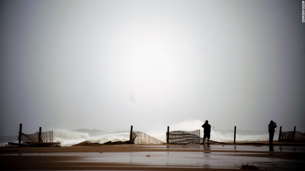 Two people stand near the edge of the boardwalk on Monday in Ocean City, Maryland.