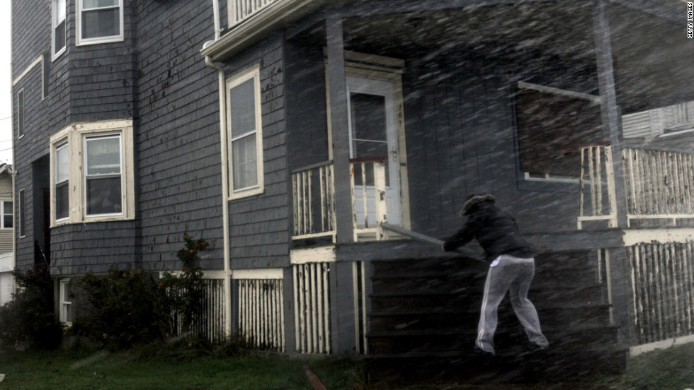 A woman examines her storm-damaged porch as heavy rain continues to pour in Winthrop, Massachusetts, on Monday.