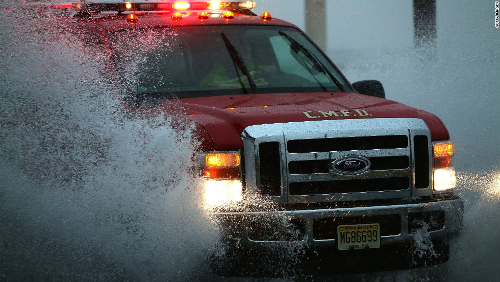 An emergency vehicle drives down Cape May, New Jersey's flooded Ocean Avenue on Monday.